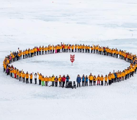 Guests and Expedition Team stand in a circle with the North Pole Sign in the middle of them. The photos is taken from the bow of the ship looking down towards the sea ice.
