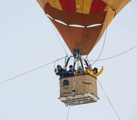 Guests wave at the camera from the basket of the tethered hot air balloon at the North Pole.