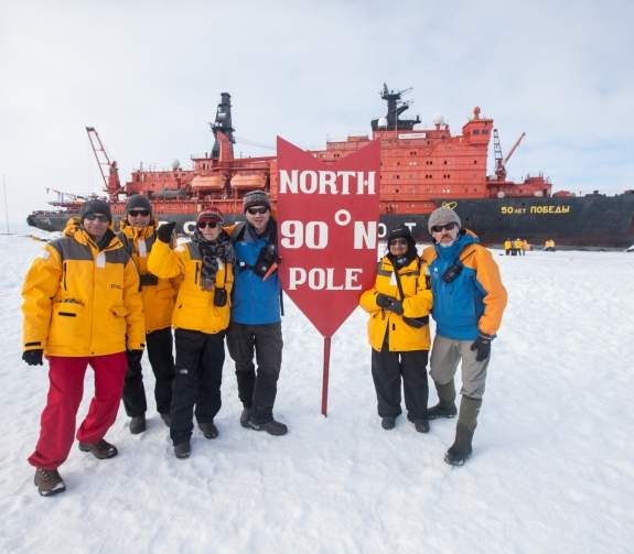 Guests and Expedition Staff members pose for a photo next to the North Pole sign, with the icebreaker 50 Years of Victory in the background.