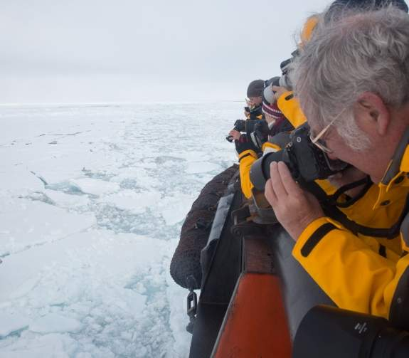 A guest looks through the view finder of their camera as they capture the photograph of the polar bear standing on sea ice below.