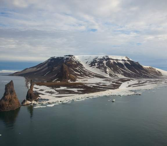 Aerial views of the snow covered peaks in the Franz Josef Land Archipelago from the helicopters onboard the 50 Years of Victory