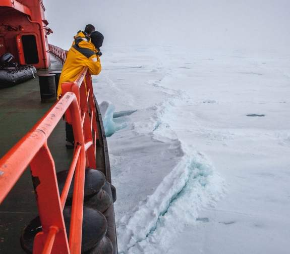 Guests look below on the port side of the vessel as it breaks up sea ice that appears to be over a meter thick.