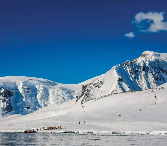 Passengers exiting Zodiac and hiking in the Antarctic