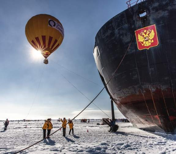 Quark Expedition Guests pose for pictures in front of the bow of the 50 Years of Victory. A hot air balloon and fellow guests can be seen on the sea ice behind them.